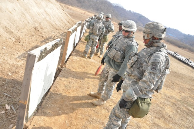 (from right) Pvt. Myshian Collins and Sgt. Joseph Downs, both assigned to 194th Combat Sustainment Support Battalion, 501st Sustainment Brigade, review a target while conducting small-arms training at Story Range near Panmunjeom, South Korea Mar. 28, 2011.