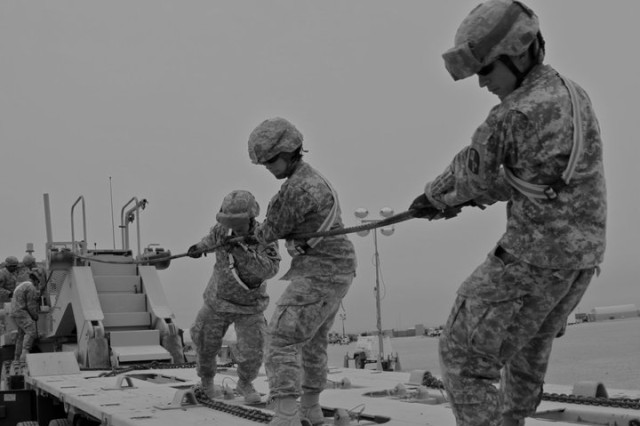 Pfc. Jessica Walter, Spc. Jacob Crainey, Sgt. Kevin Hensely, all members of the 778th Transportation Company,  unwind a winch cable during a Heavy Equipment Trailer Net training course conducted at Camps Arifjan and Buehring, Kuwait on April 2nd, 2011