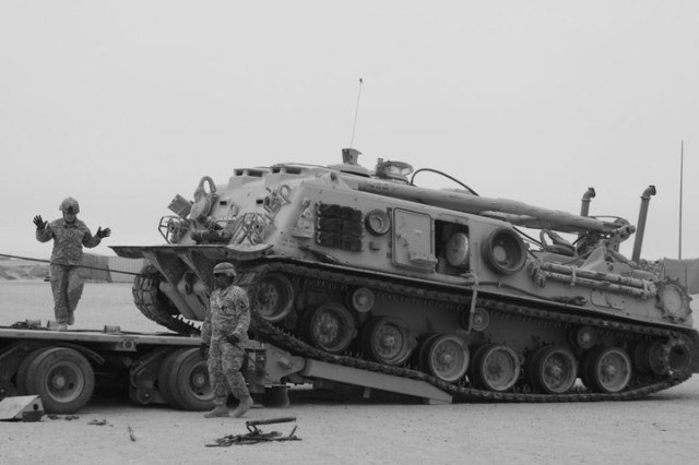 Spc. Ashley Wilson and Sgt. Keith Wilson with 778th Transportation Company help winch up an M88 Track Recovery Vehicle on to an M1000 trailer during a Heavy Equipment Transportation Licensing Qualification class conducted at Camps Arifjan and Buehring on April 2, 2011.