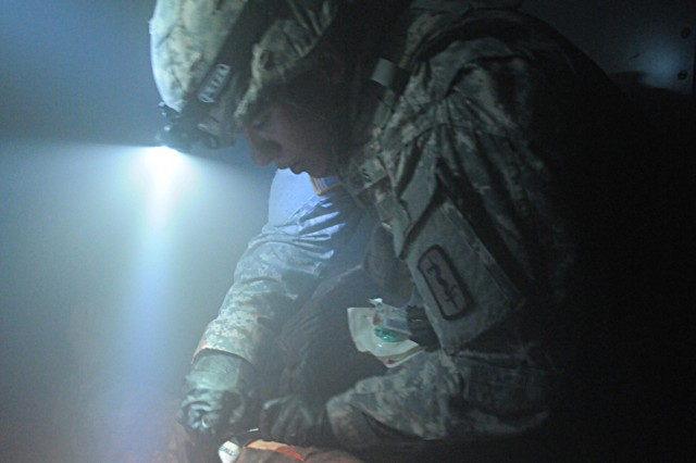 Spc. Christopher Higgins, a combat medic with the 557th Medical Company (Area Support), secures a tourniquet on a simulated casualty at the Medical Simulation Training Center in Vilseck, Germany, March 30.