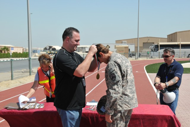 230th Special Troops Battalion's Capt. Tammy Cook receives a medal for finishing the Camp Arifjan Bataan Memorial Death March on March 20, 2011. Cook completed the march in record time for her age bracket. The Morale, Welfare and Recreation sponsered memorial march is similar to those held across the world in memory and respect for those Soldiers who were forced to march as Japanese Prisoners of War during World War II. Camp Arifjan's march took servicemembers on a 12.5 kilometer (7.75 miles) trail through sand gravel and Kuwaiti heat.
