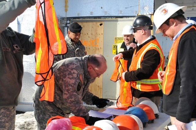In his March trip to Fort Greely, Alaska, Lt. Gen. Richard P. Formica, commander, U.S. Army Space and Missile Defense Command/Army Forces Strategic Command, signs for a construction zone hard hat and orange safety reflective vest before entering the Family and Morale, Welfare and Recreation Community Activity Center construction site. The new facility, scheduled to open in late fall of 2011, will contain an eight lane bowling alley, restaurant, classrooms, and activity rooms. Also pictured from left to right: Fort Greely Garrison Commander Lieutenant Chris W. Chronis, USASMDC/ARSTRAT; Command Sgt. Maj. Larry S. Turner; Department of Public Works supervisory general engineer Carl Ramos; Department of Public Works master planner Tim Merrymon; and recreation specialist community activities for Family and Morale, Welfare and Recreation Daniel Cain.