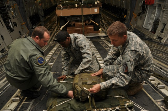 POPE ARMY AIRFIELD, N.C. - Airmen and Soldiers work together to set up the series of parachutes that will safely pull a vehicle and trailer from a C-17 Globemaster Monday. The equipment is part of a heavy equipment drop forming the first day of a three-day airborne exercise being held by the 782nd Brigade Support Battalion, 4th Brigade Combat Team, 82nd Airborne Division. (Photo by Spc. David L. Nye, 4th Brigade Combat Team, 82nd Airborne Division Public Affairs)