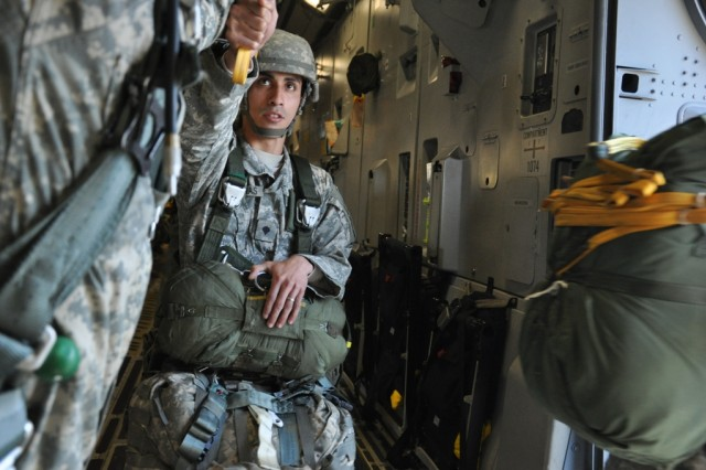 FORT BRAGG, N.C. - A Paratrooper hands his static line off to a safety as he takes his turn in the door. After exiting he will take an 800-foot fall to Luzon Dropzone, his fall arrested by the parachuite on his back. After securing his gear he will rendezvous with the rest of the jumpers and head home after another great day to be in the 82nd Airborne Division. (Photo by Spc. David L. Nye, 4th Brigade Combat Team, 82nd Airborne Division Public Affairs)