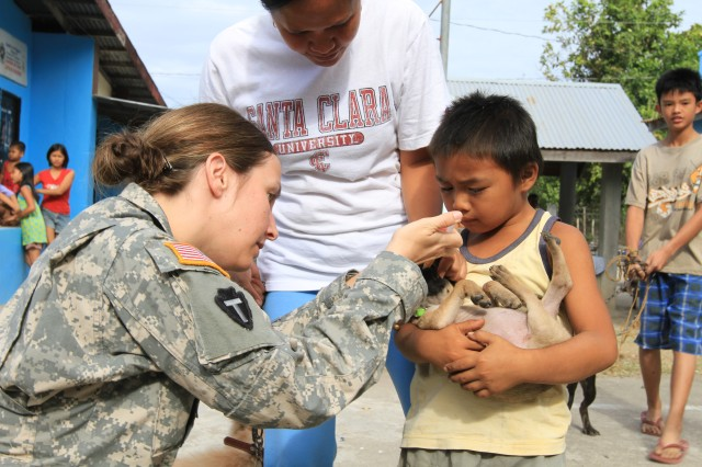 Capt. Jennifer Scruggs, veterinarian with the Balikatan 11 team, gives a puppy dewormer during a veterinary civic action project in San Antonio, Philippines, as part of Balikatan 2011, March 28-29. Balikatan is a bilateral military exercise between the Philippines and the United States. Humanitarian assistance and training activities enable the Filipino and American servicemembers to build lasting relationships, train together, and provide assistance in communities where the need is the greatest. They improve their ability to operate as one team in joint projects. Scruggs is from the Western Pacific District Veterinary Command.