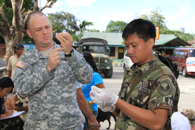 Staff Sgt. James Barclay (left), animal care specialist, and Philippine Air Force Staff Sgt. Carlo Magno Tamondong, veterinary technician, prepare rabies shots during a veterinary civic action project March 28-29, in San Antonio, Philippines, as part of Balikatan 2011. Barclay is from the Western Pacific District Veterinary Command. Balikatan is a bilateral military exercise between the Republic of the Philippines and the United States. Humanitarian assistance and training activities enable the Filipino and American servicemembers to build lasting relationships, train together, and provide assistance in communities where the need is the greatest. They improve their ability to operate as one team in joint projects.