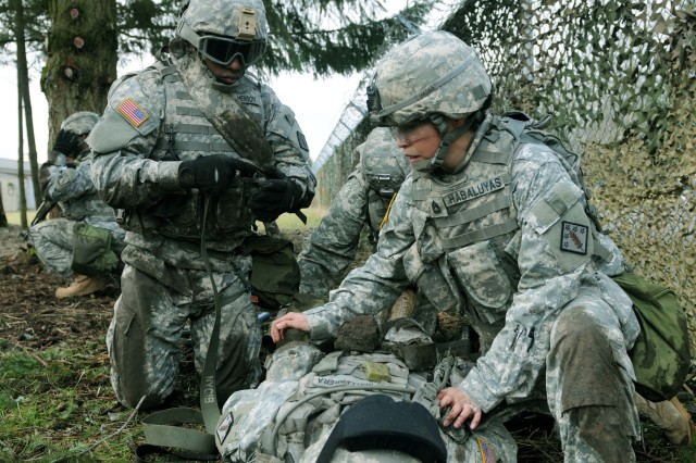 Sgt. 1st Class Jacqueline Habaluyas, chemical specialist, 61st Chemical Company, a Seattle native, helps Pvt. Lonnie Henson, chemical specialist, 61st Chemical Company, a Dallas native, secure a patient to a litter before transporting the patient to a safe zone at the Medical Simulation Training Center on Joint Base Lewis-McChord, Wash., during the Tactical Combat Casualty Course, March 10. The TC-3 obstacle course gives Soldiers an opportunity to put the skills they learned in the classroom to use in a field environment.   110310-A-DJ549-139