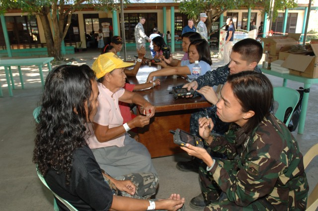 Philippine Army 2nd Lt. Alma Mae Maquido, civil military operations officer, 24th Infantry Battalion, assess a patient at the triage station at the medical civic assistance project held March 31, at the Pundakit Elementary School, Philippines, as part of Balikatan 2011. Balikatan is a bilateral annual exercise between the Philippines and the United States. Humanitarian assistance and training activities enable servicemembers to get to know each other, train together, and provide assistance in communities where the need is the greatest.
