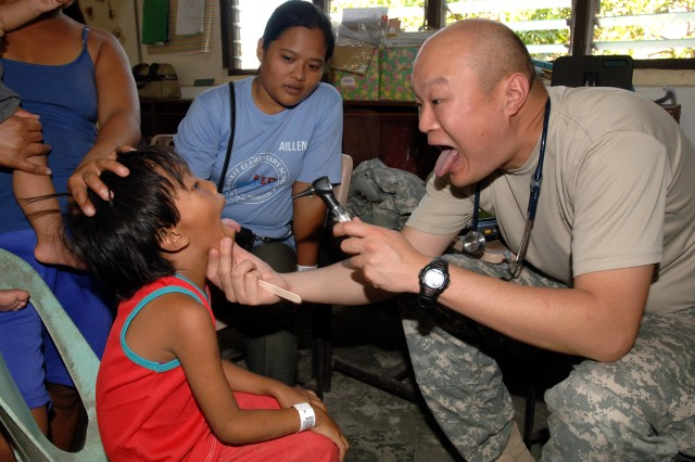 """Capt. James Ham, emergency physician with the 130th Engineer Brigade, Schofield Barracks, Hawaii, gets a patient to """"open wide"""" March 31, at a medical civic assistance project held at the Pundakit Elementary School in the Philippines as part of Balikatan 2011."""