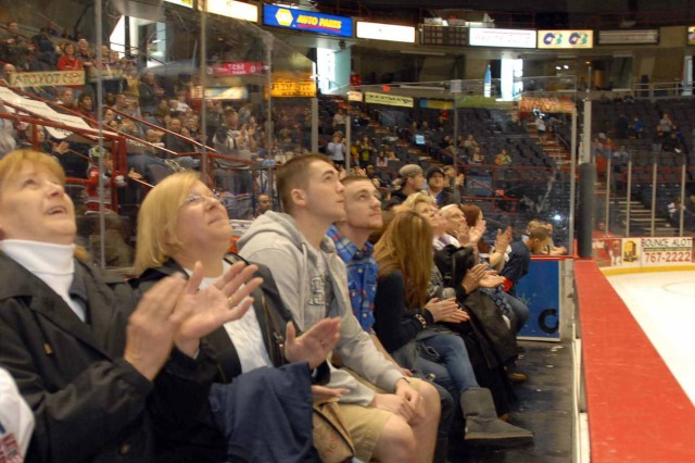 ALBANY, NY--Families of the 501st Ordnance Battalion Soldiers look up as the Soldiers appear on the Times Union Center's Jumbotron during an Albany Devils hockey game April 3.