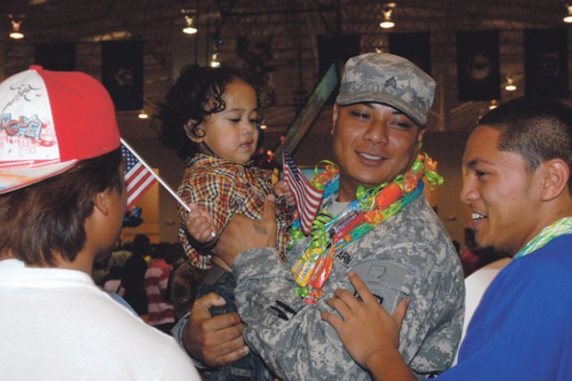 Sgt. Frank Solia, of the 13th Combat Sustainment Support Battalion, is greeted by relatives. Friends and family members came out to Freedom Hall Saturday night to welcome the 13th CSSB back after a yearlong deployment in Iraq.
