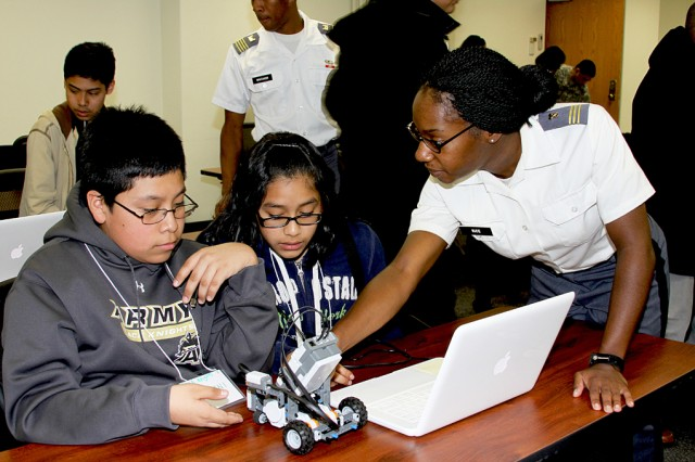 West Point Class of 2011 Cadet Myea Rice shows eighth grader Gionvanni Balbuena and seventh grader Yenifer Flores, both from Yonkers, some steps in programming a robot at the Black Engineering Expo April 2 at Thayer Hall. The West Point chapter of the National Society for Black Engineers hosted the expo at Thayer Hall for seventh and eighth graders from Yonkers and the Bronx.