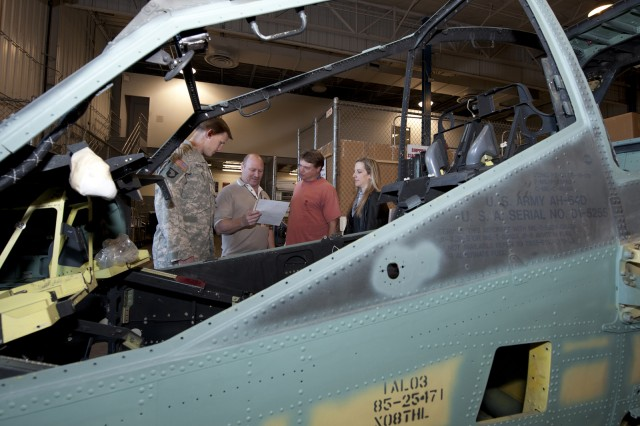 Defense and Boeing representatives examine the paperwork that accompanied the fuselage of the first AH-64D Apache Block III helicopter upon its arrival at the Mesa, Ariz., receiving dock, Jan. 28, 2011.