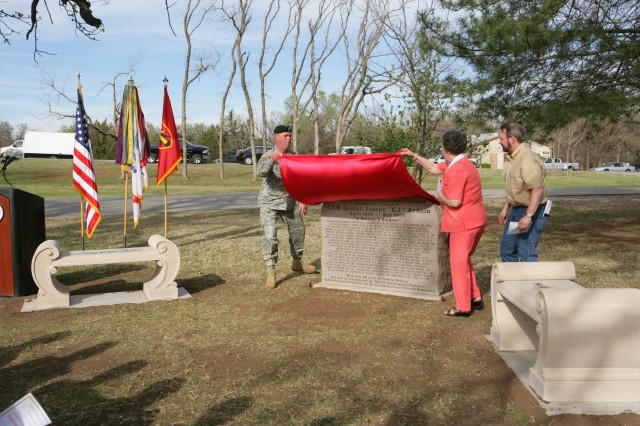 Maj. Gen. David Halverson, Fires Center of Excellence commanding general, and Nellie Ardoin, wife of the late E.J. Ardoin, lift a shroud off a memorial placed in Ardoin's honor during a ceremony April 1. The memorial provides some information about Ardoin and stands near the entrance to the Command Sgt. Maj. E.J. Ardoin Natural Resources and Enforcement Compound.
