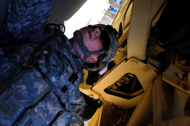 """Private Jonathon Burson, 3/7 Cav., 2HBCT, 3rd ID, inspects a HMMWV during the Saber Wrench Academy's """"Best Mechanic"""" competition held March 25."""