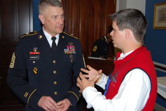 Sgt. Maj. of the Army Raymond F. Chandler III listens to National Guard representative Matthew Constantine, 16, during an Army Teen Panel luncheon on Capitol Hill Apr. 7.  The Army Teen Panel provided teenagers a chance to share their experiences and thoughts on being part of a Military Family with members of the Congressional Military Family Caucus and senior Army leadership.