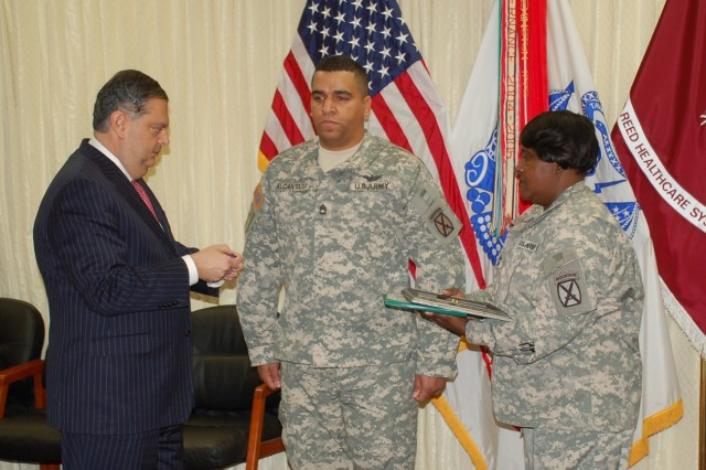 Former Secretary of Energy Spencer Abraham awards Sgt. 1st Class Irwin Alcantara with the Purple Heart Medal at Walter Reed Army Medical Center, Washington, D.C.
