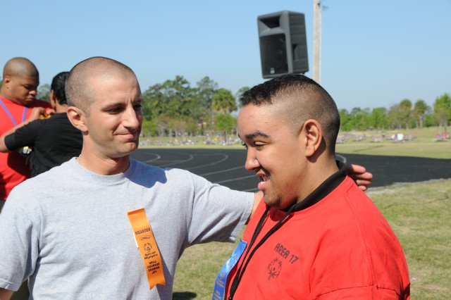 Private Justin Custidio, DHHB, congratulated Darnel Minor, 17, a Special Olympics athlete from Liberty County High School, for winning first place in the 50-meter run, March 25, at the Fort Stewart Quick Track.