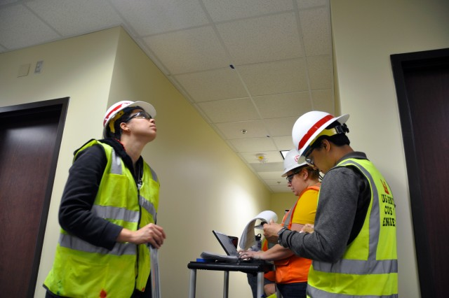 "(L-R) Ekaterina Dones, civil engineering intern, U.S. Army Corps of Engineers (USACE), Kristina Schafer, electrical quality assurance engineer, Hensel Phelps Construction Co., and Dale Reeves, construction control intern, USACE, check ceiling installation work during the pre-final inspection of U.S. Army Forces Command (FORSCOM) office areas on the 1st floor of the FORSCOM/U.S. Army Reserve Command Combined Headquarters Construction Project, March 31, 2011, at Fort Bragg, N.C. Discrepancies are ""punch-listed"" for resolution before the 631,000 sq. ft. complex is transferred from the construction company to the U.S. Army, June 21, 2011."
