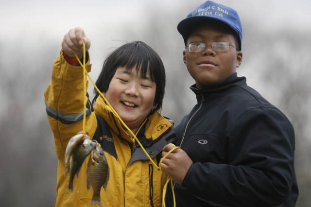 Dylan Fauz, 11, of Severn and Melvin Diggs, 11, of Springdale, show off their catches Saturday at the Fishing Rodeo. The Maryland Department of Natural Resources stocked Burba Lake with rainbow trout, bass and bluegills prior to the four-hour event.