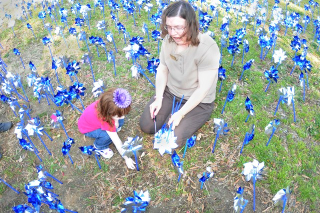 Elaine Sexton, Army Community Service, helps 2 year-old Shelby Gardner plant pinwheels to mark National Child Abuse Prevention Month.