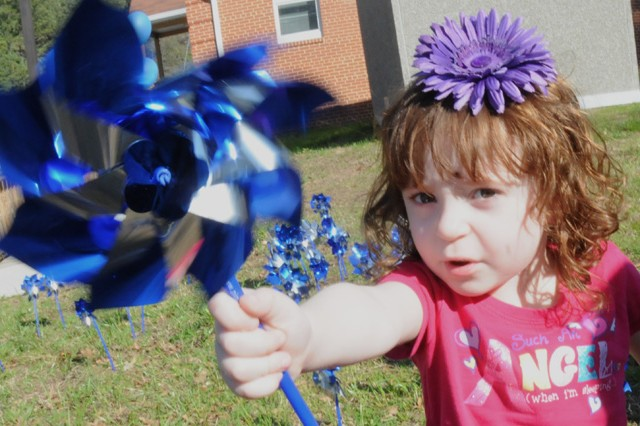 Two-year-old Shelby Gardner offers a pinwheel.