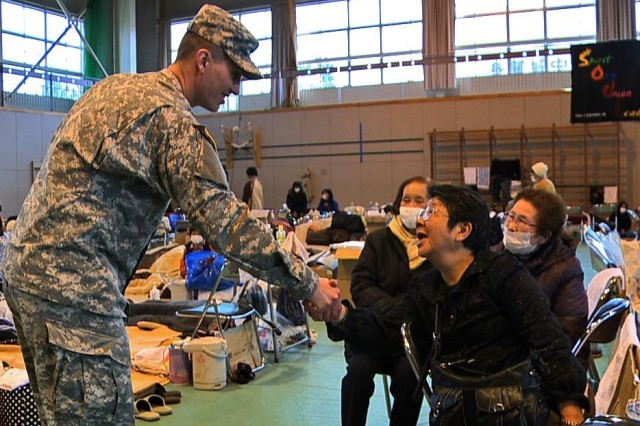 Staff Sgt. Ryan Knight, a soldier with U.S. Army Japan, shakes hands with a displaced Japanese citizen during the relief efforts of Operation Tomodachi at Toho Junior High School, March 31. The high school is being used as a shelter for the displaced citizens following the recent earthquake and tsunami that impacted the area.