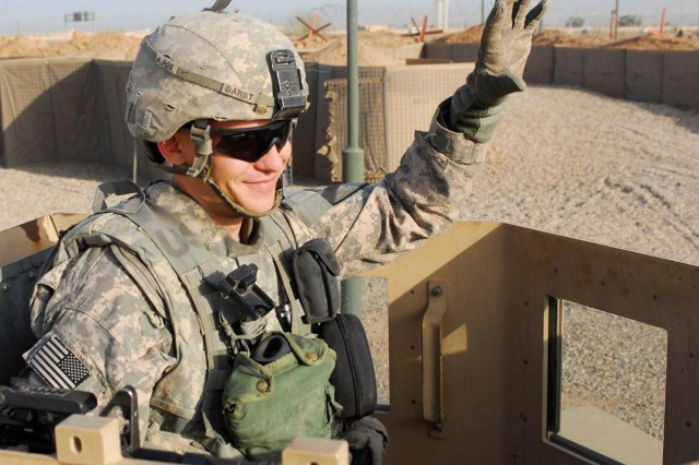 CONTINGENCY OPERATING SITE WARRIOR, Iraq - Spc. Shane Darst, an armor crewmember serving with Company D, 2nd Battalion, 12th Cavalry Regiment, attached to the 1st Advise and Assist Task Force, 1st Infantry Division, waves at a passing patrol near Contingency Operating Site Warrior, near Kirkuk, Iraq, April 3, 2011.
