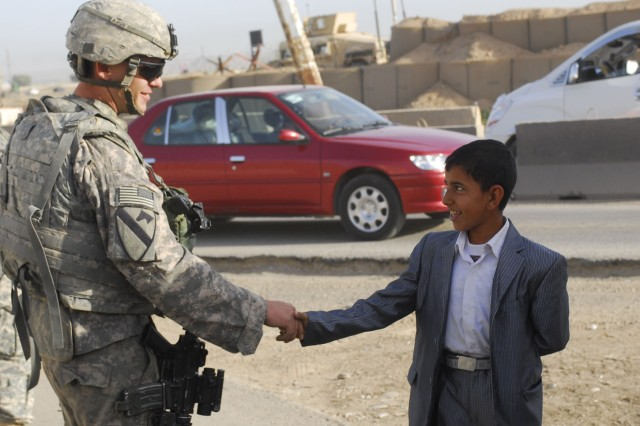 CONTINGENCY OPERATING SITE WARRIOR, Iraq - Spc. Shane Darst, an armor crewmember serving with Company D, 2nd Battalion, 12th Cavalry Regiment, attached to the 1st Advise and Assist Task Force, 1st Infantry Division, shakes hands with a young child at a checkpoint near Contingency Operating Site Warrior, Iraq, April 3, 2011.