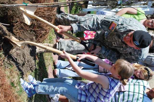 After reading his proclamation declaring March 18 Arbor Day on post, Fort Bragg Garrison Commander Col. Stephen J. Sicinski helps students of the Devers Elementary School plant a tree in the garden behind the school. At the ceremony attended by students, teachers and other members of the community, Cumberland County Ranger Andrew Snyder presented school to Kyle Dow from the school's Flag Team. Snyder also presented the colonel with the Tree City USA Award and the Tree City Growth Award recognizing the post's support of values and practices of the Arbor Day movement throughout the year.