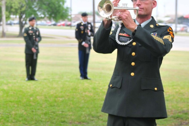 FORT HOOD, Texas - Sgt. 1st Class Andrew Phelps, a bugler with the 1st Cavalry Division Band, plays taps during the 15th Brigade Support Battalion's Memorial Ceremony for Spc. Justin Richardson on Fort Hood, Texas, April 7.