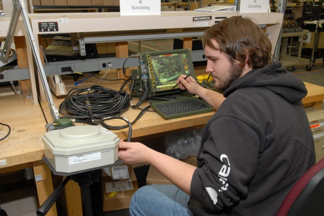 Kyle White, electronics worker, adjusts a Blue Force Tracking System transponder while using a fault test verification kit to screen a KGV-72 encryption device. The process takes about an hour to complete.