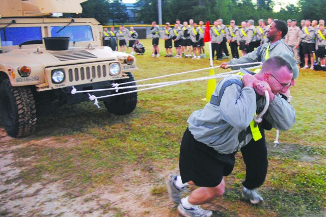 These three 83rd Chemical, Biological, Radiological, Nuclear and Explosive Battalion team members, Pfc. James Chrane (front), Spc. Robert Lawrence (middle) and 2nd Lt. Derrick Williams (back) finished in third place in the Fort Polk Intramural Sports Program's Truck Pull contest April 6. Steering the vehicle was 2nd Lt. Brandon Jack.