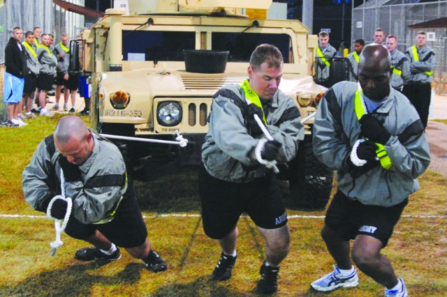 Spc. Phillip Stallings (left), Spc. Michael Embrey (center) and Staff Sgt. Edward Huggins, 209th Military Police Company, 519th Military Police Battalion, 1st Maneuver Enhancement Brigade, pull a HMMWV over a 20-meter course during the Fort Polk Intramural Sports Program's Truck Pull contest April 6 at the Soldiers Sports Complex. Steering the vehicle is Spc. Darby Parker. The team finished in third place, while the 209th's other entry in the event claimed first place.