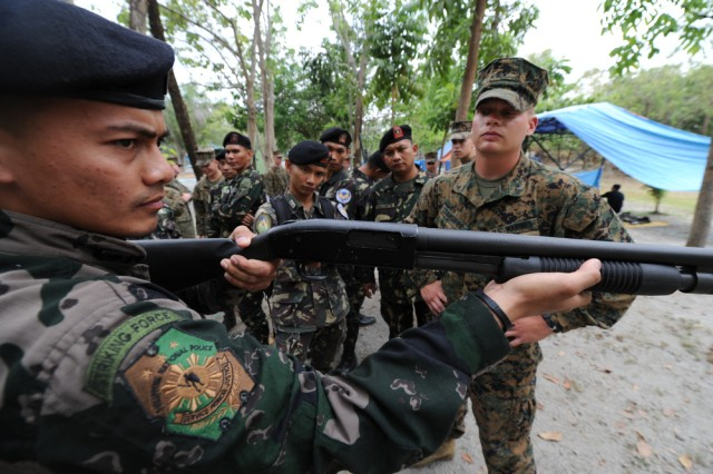 "Lance Cpl. Jeremy Standifer (right), a native of Griffin, Ga. and currently assigned to Combat Logistics Battalion 4, Camp Foster, Okinawa, Japan instructs Police Inspector, 1Lt. Ferdinan Floreca on the use of the Mossberg 500 Shotgun during a weapons familiarization seminar between U.S. Marines and Philippine Airmen during Exercise Balikatan 2011 on April 7 at Clark Field, Philippines. Balikatan means ""shoulder to shoulder"" in Tagalog and is an annual Republic of the Philippines and United States bilateral military humanitarian assistance and training exercise that is taking place in the Philippines April 5-15. The training helps maintain readiness and sustain the long-term security assistance relationship shared between the two countries."