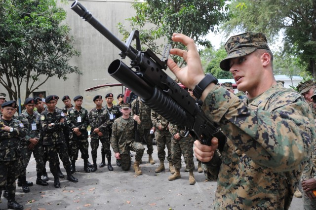 "Cpl. William McDougall, a native of Columbia, Ky. and currently assigned to Combat Logistics Battalion 4, Camp Foster, Okinawa, Japan demonstrates the use of the M-203 grenade launcher to fellow CLB-4 Marines and members of the Philippine Air Force during a weapons familiarization seminar between U.S. Marines and Philippine Airmen during Exercise Balikatan 2011 on April 7 at Clark Field, Philippines. Balikatan means ""shoulder to shoulder"" in Tagalog and is an annual Republic of the Philippines and United States bilateral military humanitarian assistance and training exercise that is taking place in the Philippines April 5-15. The training helps maintain readiness and sustain the long-term security assistance relationship shared between the two countries"