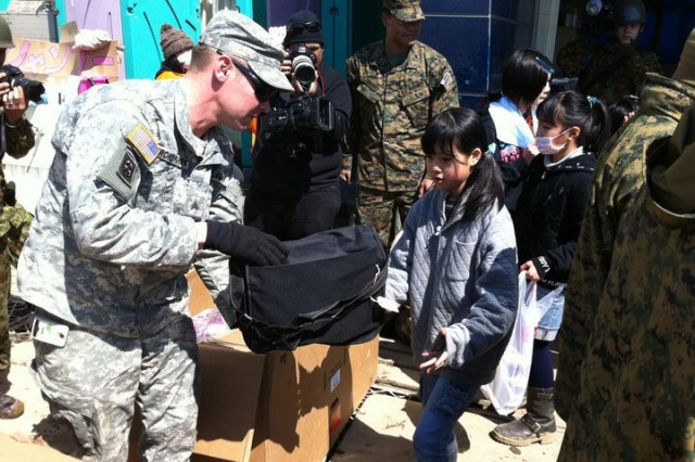 Soldiers and Marines stationed in Japan pass out school supplies April 5, to Japanese children during Operation Backpack.