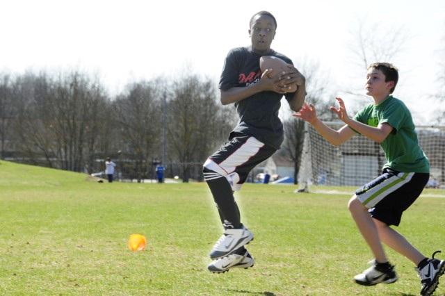 Eighth-grader Anthony Maynard catches the ball while seventh-grader Peyton Wilson blocks during a running drill, April 2. Both students attend Netzaberg Middle School.