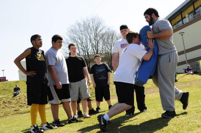 Vilseck High School sophomore Bryan Smith rushes Frankfurt Universe lineman Andrew Ciukurescu during an offensive drill while fellow teammates look on. The Frankfurt Universe team practiced with military children and teens during the two-day football clinic to improve the students' skills.