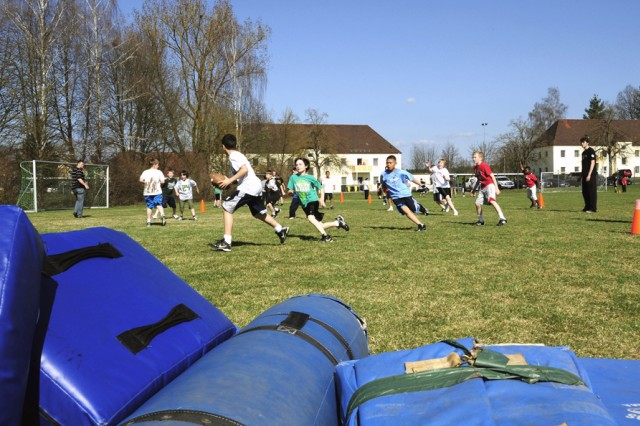Young footballers participate in a game with guidance from the Frankfurt Universe American football team during a two-day football clinic held on Rose Barracks. The team members shared their skill and love of the game with more than 50 students within the Grafenwoehr community.
