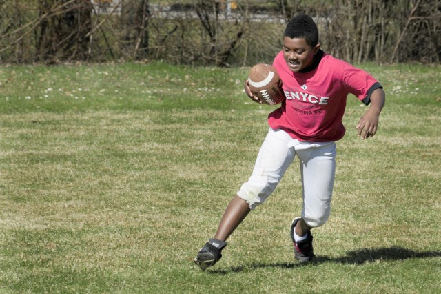 Denzel Washington, a third-grader at Vilseck Elementary School, runs with the ball during the two-day football clinic held on Rose Barracks.