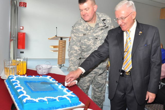 Col. Jeffrey Dill, USAG Wiesbaden commander, and Dr. Robert Schloesser, director of Family, Morale, Welfare and Recreation, cut a ceremonial cake to mark the signing of the Employee and Customer Covenant.