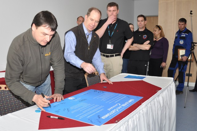 Larry Harmon (from left), Peter Witmer, Aaron Chapuis and fellow U.S. Army Garrion Wiesbaden Family, Morale, Welface and Recreation employees sign the Employee and Customer Covenant at the Wiesbaden Entertainment Center April 1.