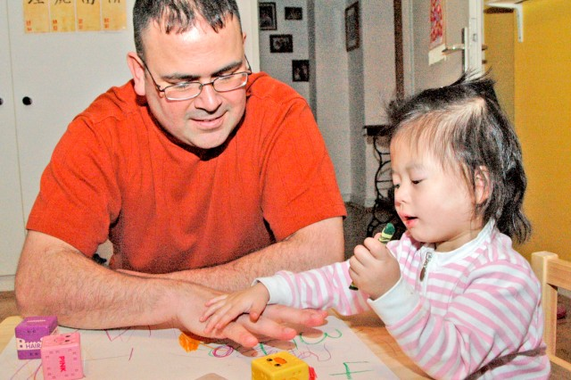 Master Sgt. Matthew Shea, with 1st Armored Division, plays with his daughter Ilana Ji-Lin Shea. Matthew and his wife Heidi adopted Ilana from an orphanage in mainland China in 2010.