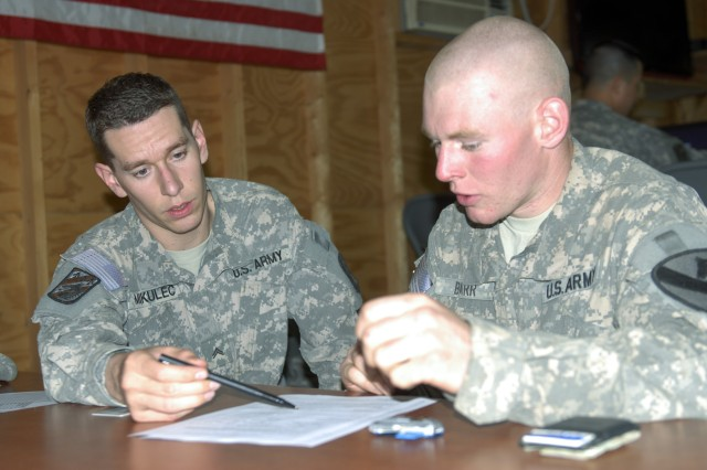 CONTINGENCY OPERATING BASE ADDER, Iraq - Cpl. Brad Mikulec (left), a financial management technician with 9th Financial Management Company, 3rd Sustainment Brigade,  helps Pfc. Emery Barr, a cavalry scout with D Company, 3rd Battalion, 8th Cavalry Regiment, 3rd Advise and Assist Brigade, 1st Cavalry Division, set up a Savings Deposit Program account while on a mobility mission to al-Sheeb, Iraq. The finance team and personnel with AAFES visit Soldiers in remote locations once a month.