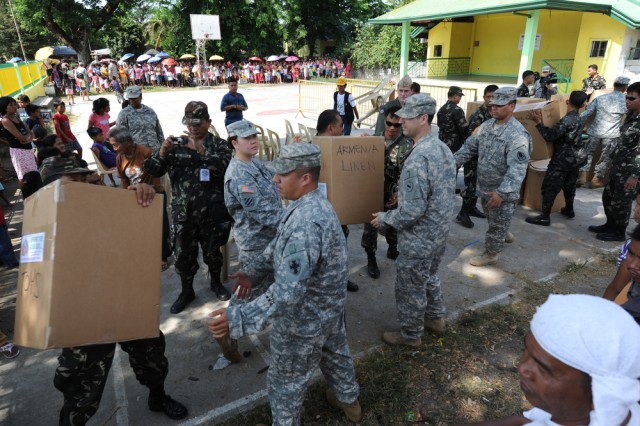 "U.S. Soldiers, Sailors, Airmen and members of the Philippine Army unload donated items April 8, 2011, in Barangay Armenia in the Tarlac region of the Philippines, during Exercise Balikatan 2011. The four remote Barangays that received the donations were Armenia, San Jose De Urquico, Maasin Pura and San Carlos. Balikatan means ""shoulder to shoulder in Tagalog and is an annual Republic of the Philippines and United States bilateral military humanitarian assistance and training exercise that takes place in the Philippines. The training helps maintain readiness and sustain the long-term security assistance relationship shared between the two countries."