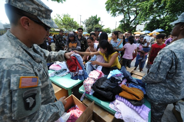 "Maj. Iven Sugai (left) with U.S. Army Pacific, unloads clothes while U.S. servicemembers and members of the Philippine Army hand out donations of clothes, linen and toys to residents of Barangay Armenia while at Armenia Elementary School, Philippines, April 8, 2011, during Exercise Balikatan 2011. Balikatan means ""shoulder to shoulder in Tagalog and is an annual Republic of the Philippines and United States bilateral military humanitarian assistance and training exercise that takes place in the Philippines. The training helps maintain readiness and sustain the long-term security assistance relationship shared between the two countries."
