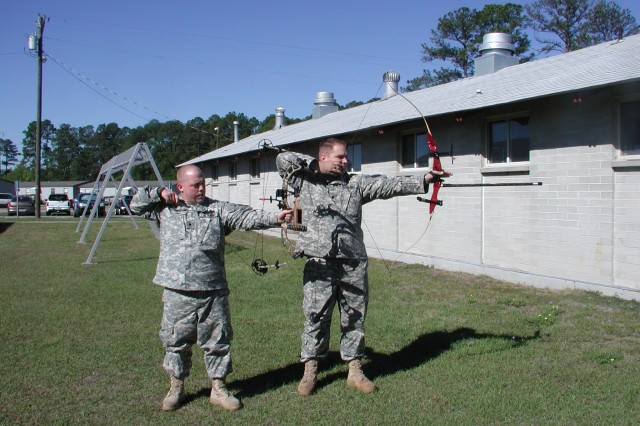 Spc. Zachariah Smith, left, and Spc. Stuart Lancaster demonstrate an archery stance. Both soldiers will compete in the paralympic Warrior Games next month.