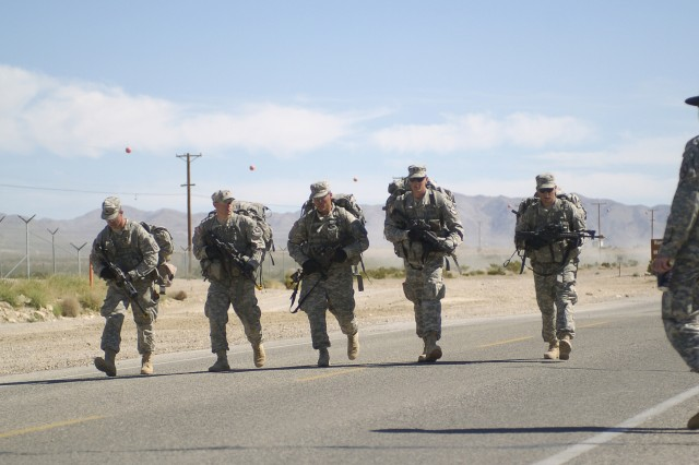 FORT IRWIN, Calif-A team of Soldiers cross the end of point of a 12-mile road march during 2nd Squadron's Spur Ride, April 5. (Photo by Sgt. Giancarlo Casem, 11th ACR Public Affairs)
