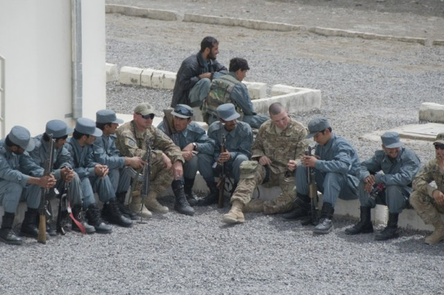 TAKHTEH POL, Afghanistan - Afghan National Police and U.S Army Soldiers from Bravo Company, 4th Squadron, 70th Armored Regiment, 170th Infantry Brigade Combat Team sit together outside the ANP's newly renovated police station in Takhteh Pol, Afghanistan, April 11, 2011. Leaders from the Afghan law enforcement community, and ISAF and local citizens gathered for a ribbon cutting ceremony to celebrate the building's reopening. (photo by Senior Airman Jessica Lockoski)